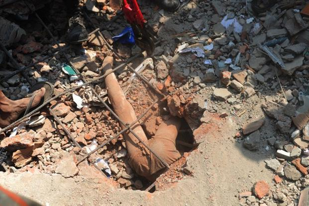 The dead body of a Bangladeshi youth is seen in the rubble. The incident coming within months of the devastating fire at the Tazreen Fashion factory in November, raises serious concerns about worker safety and low wages in the country. AFP