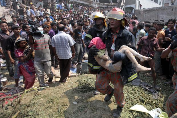 Rescue workers carry a young victim's body after the collapse. Some 2,000 people were present in the building when it collapsed on Wednesday. The death toll may rise as there are still lots of people trapped under the building's rubble. AP