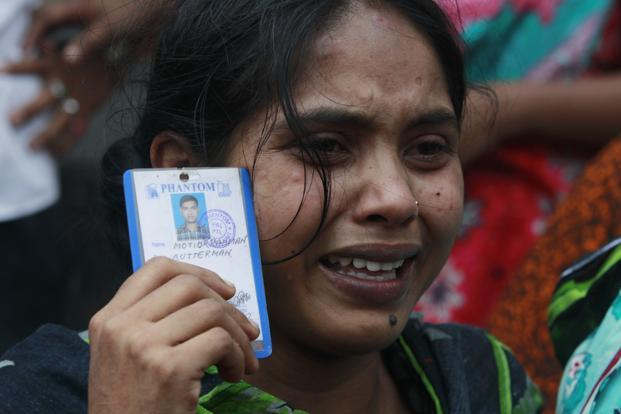 Relatives of the workers swamped the site of the collapse, wailing, waiting and praying for the survival of their loved ones. Here: Johura, 20, holds a picture of her missing husband Motiur Rahman, who was working in the building. Reuters