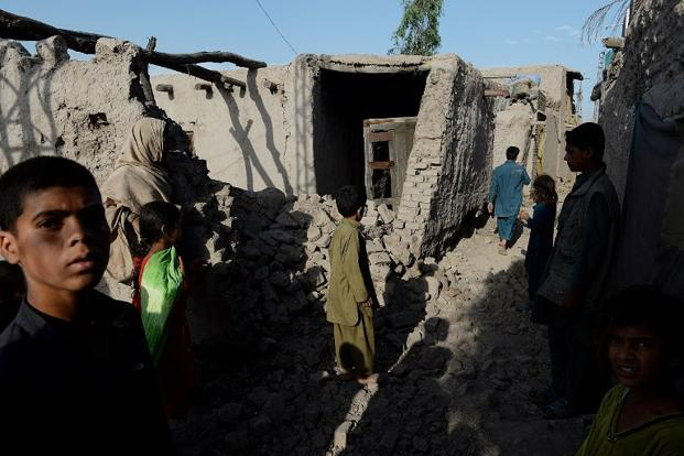 Afghan residents stand near their homes damaged by a powerful earthquake in Charbagh village in Nangarhar province on Wednesday. Photo: Shah Marai/AFP