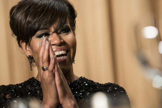 US first lady Michelle Obama laughs as she sees Obama's photos with bangs, during the White House Correspondents Association Dinner. AFP