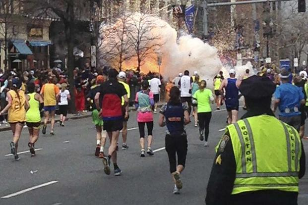 In a file photo, runners continue to run towards the finish line of the Boston Marathon as an explosion erupts near the finish line of the race. Photo: Reuters