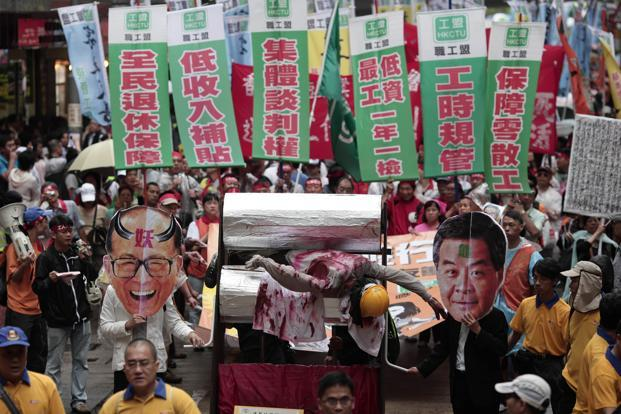 A file photo of protesters hold masks of Hong Kong chief executive Leung Chun-Ying (front right) and Asia's richest man Li Ka-shing (front left) as they push a mock meat grinder containing a dummy of a dock worker (centre) at a May Day rally in Hong Kong. Photo: AFP (AFP)