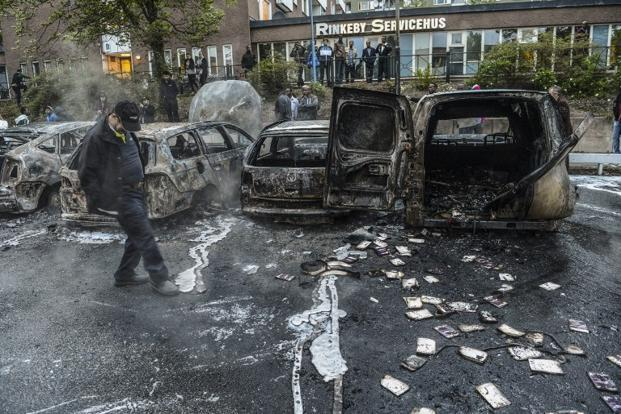 A bystander checks the debris of a burnt out cars in the Stockholm suburb of Rinkeby after youths rioted in several different suburbs around Stockholm, Sweden for a fourth consecutive night on 23 May 2013. Photo: AFP