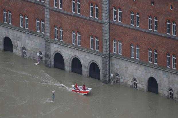 Members of the Red Cross make their way through the flooded old centre of Passau in Germany. The markers set in 1954, when the city suffered its worst flooding in living memory, have disappeared beneath the rising water. AP