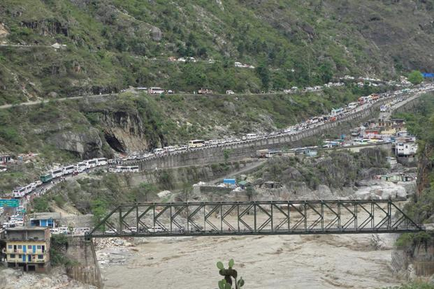Stranded vehicles stand in queues after heavy rains destroyed roads and bridges in Uttarakhand on 17 June. Reuters