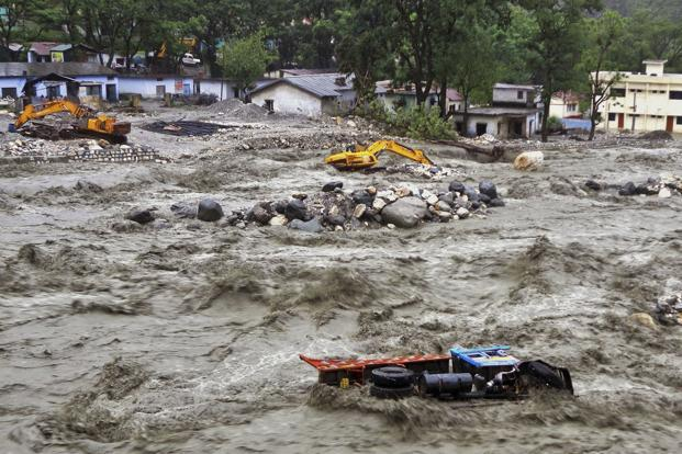 Bulldozers and other vehicles are adrift in a flooded river in Uttarkashi district. Torrential rain and floods washed away buildings and roads, leaving thousands stranded after landslides. AP