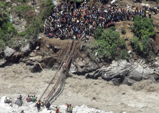 ITBP personnel, in uniform, help stranded pilgrims on a makeshift