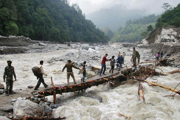 Indian army personnel help stranded people cross a flooded river after heavy rains in Uttarakhand on Sunday. Photo: Reuters