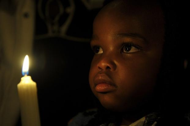 A child holds a candle as he prays for Nelson Mandela, outside the Medi-Clinic Heart Hospital where he is being treated in Pretoria. Mandela has been in hospital since 8 June.  AFP
