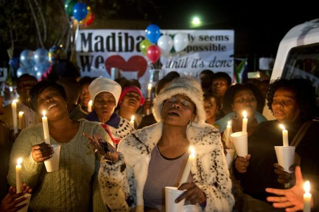 A group of well-wishers hold up candles outside the hospital as they pray for the recovery of Mandela. Hundreds continue to gather outside the Pretoria hospital with messages of support for their beloved Madiba. AFP