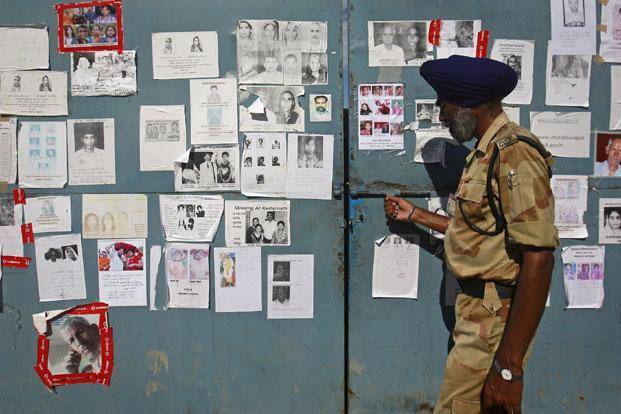 A securityman opens a gate covered in posters of missing people, affected by the flash floods and landslides, at the Indian Air Force base in Dehradun, in Uttarakhand on 26 June 2013. Photo: Reuters