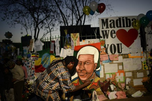 A man paints a portrait of Nelson Mandela outside the hospital. Mandela has been hospitalised four times since December, mostly for a recurring lung infection dating back to his time in jail for protesting against the apartheid government. Reuters