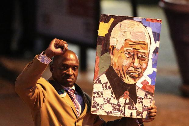 A well-wisher carries a portrait of Nelson Mandela outside the Pretoria hospital. Mandela retired from public life in 2004 and has played no active role in the ruling African National Congress since then concentrating instead on charitable work. Reuters