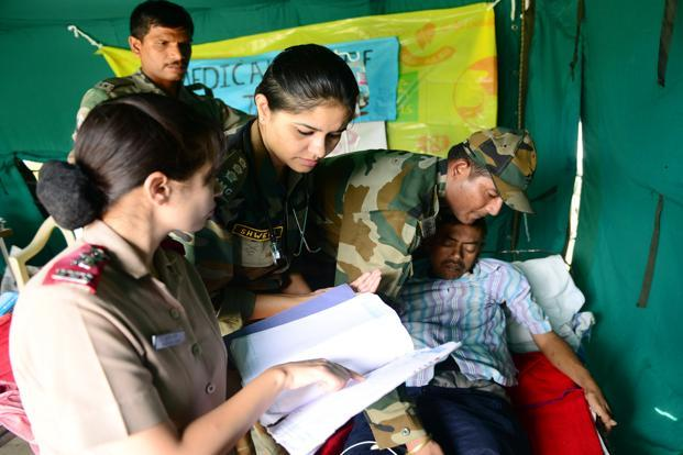 Army medical officers work inside a makeshift tent next to the helipad at the Joshimath rescue base.