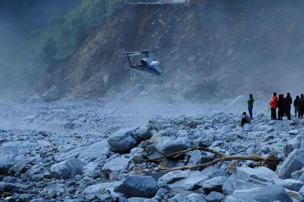 A civilian helicopter involved in rescue operations makes a tough landing on the riverbed at Govindghat. Photo: Ramesh Pathania/Mint
