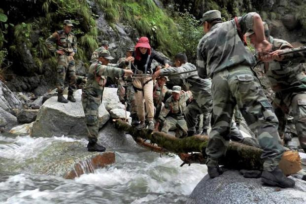 An Indian army soldiers rescue a woman at Pindari Glacier, in the northern Indian state of Uttarakhand on 27 June 2013. Photo: AP (AP)