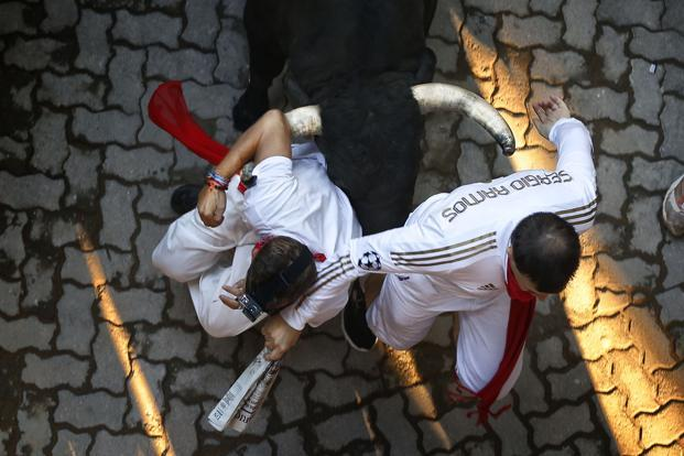 Revelers are chased by a Victoriano del Rio ranch fighting bull during the running of the bulls. The run ends in the Pamplona's bull-ring. Bull-runs are held between the 7th and the 14th of July each year. AP