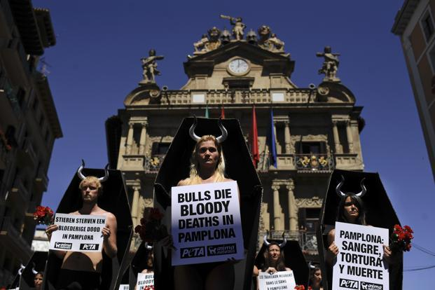 Anti-bullfighting demonstrators protest against the running of the bulls, while standing in cardboard coffins and holding red flowers, on the Ayuntamiento Square in Pamplona. AP