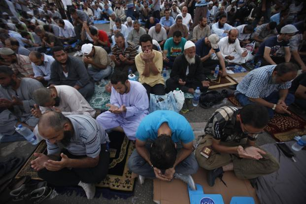 Supporters of deposed Egyptian President Mohamed Mursi recite prayers as they wait to break fast on the first day of Ramadan at the Rabaa Adawiya square where they are camping in Cairo. Photo: Reuters