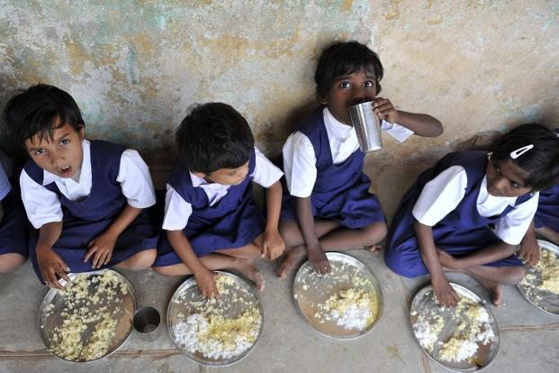 Schoolchildren eat food served as part of the mid-day meal scheme in Hyderabad on 23 June 2010. The main objectives of the programme is to protecting children from classroom hunger and to increase school enrolment. AFP