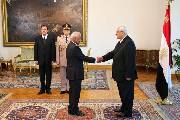 This image released by the Egyptian Presidency on Tuesday shows interim president Adly Mansour (right) shaking hands with prime minister Hazem el-Biblawi during a sweararing-in ceremony for new cabinet ministers at the presidential palace in Cairo, Egypt. Photo: AP/Egyptian Presidency