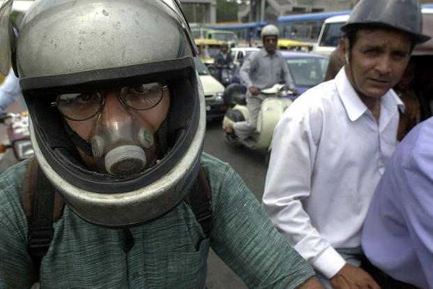A motorcyclist wears an air-filter in Delhi. The higher costs for outdoor air pollution are primarily driven by an elevated exposure of the urban population to particulate matter pollution that results in a substantial cardio-pulmonary diseases, says the report. AFP