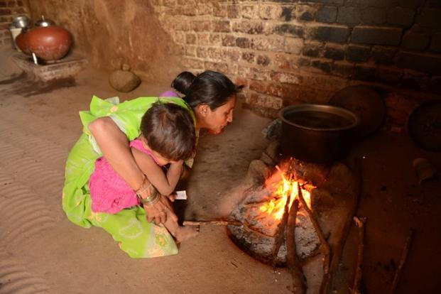 A woman holds her child while blowing to ignite her traditional stove in the village of Keiyal, Ahmedabad. According to the report, indoor air pollution stems from burning of wood, mainly in rural India. AFP