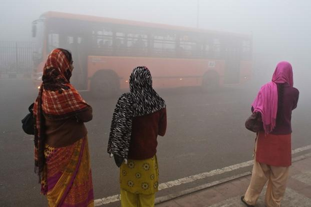 Commuters wait for a bus on a polluted morning in New Delhi on 31 January 2013. Pollution and other environmental degradation cost India $80 billion every year, the World Bank said in a report released Wednesday. AFP