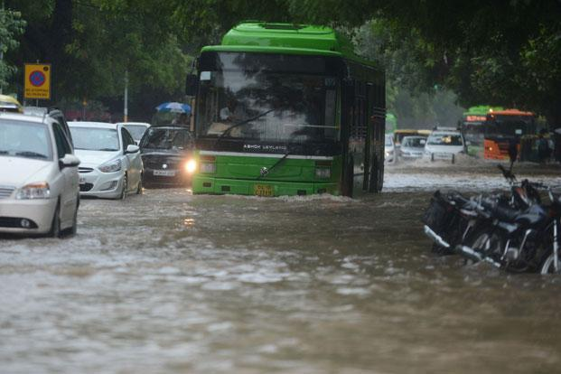 A bus tries to cross a water logged street during heavy downpour in New Delhi on Sunday. Photo: AFP (AFP)