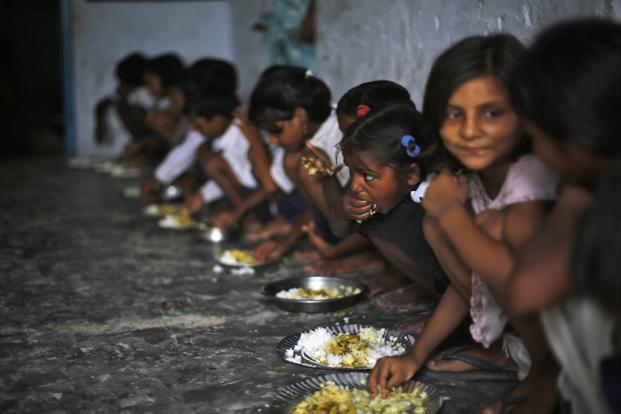 School children eat their free mid-day meal, distributed by a government-run primary school, at Brahimpur village in Chhapra district of Bihar. Photo: Reuters