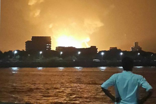 A man watches Indian Navy submarine INS Sindhurakshak on fire in Mumbai on 13 August. A huge explosion and fire have destroyed India's most advanced diesel-electric submarine, which was docked at a high-security military dockyard in Mumbai. Reuters
