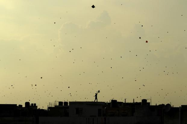Against a yellowing sky a boy flies a kite from the roof of a house in the old quarters of Delhi as people celebrate the country's Independence Day on 15 August. AP