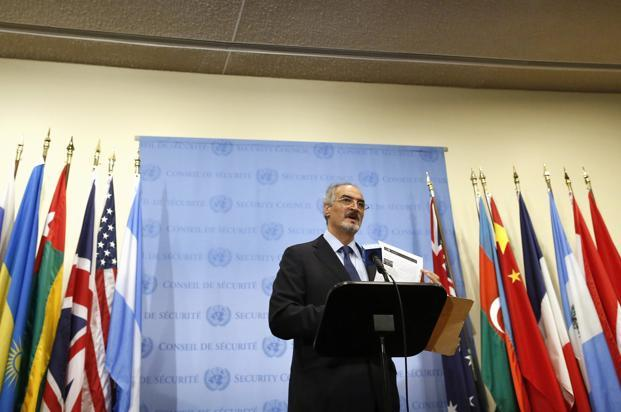Syrian UN ambassador Bashar Ja'afari shows a document to reporters at the United Nations Headquarters in New York on Thursday. Photo: Brendan McDermid/Reuters