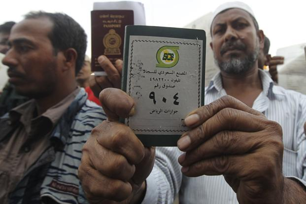 A foreign worker displays his passport as he waits outside a labour office, after missing a deadline to correct his visa status, in Riyadh. Photo: Reuters