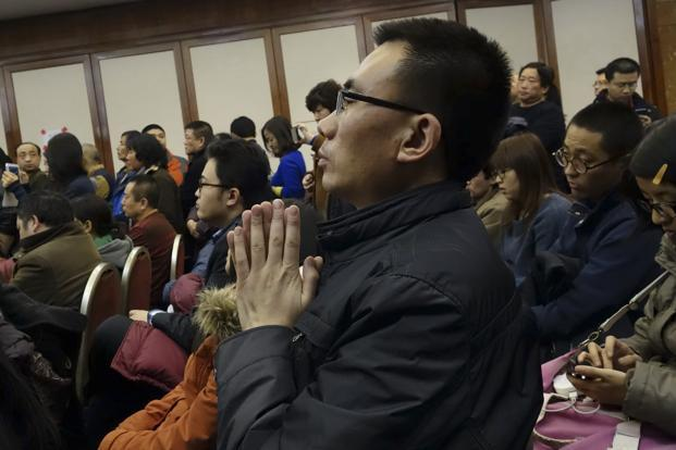 A relative of Chinese passengers aboard Flight MH370 prays at a gathering in Beijing. 10 nations including the US are taking part in the search and rescue operations with 40 ships and 34 aircraft. However, no clues have been found yet. AP