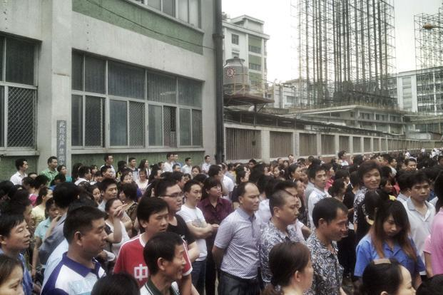 Workers gather during a strike inside the factory area of Yue Yuen  Industrial, in Dongguan