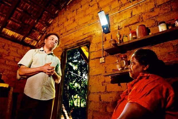 Harish Hande visits Rosamma Vergies in Vandse village, Karnataka. Her home is fitted with a two-light solar system. Photo: Gireesh GV