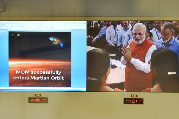 Prime Minister Narendra Modi is seen on a screen as he greets scientists alongside a graphic of the Mars Orbiter Mission after the spacecraft successfully entered the Mars orbit. Photo: AFP
