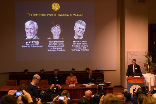 A giant screen displays the image of British-American researcher John O'Keefe and Norwegian duo May-Britt Moser and Edvard I Moser at a press conference of the Nobel Committee. Photo: AFP