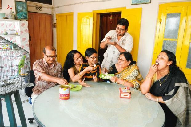 Three generations of a family in Maniktala savour KC Das 'rossogolla'. Photographs by Indranil Bhoumik/Mint