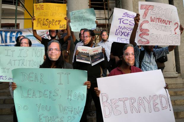 Protesters wearing masks with the image of TCS chief executive N. Chandrasekaran in Bengaluru on 17 January. Photo: AFP