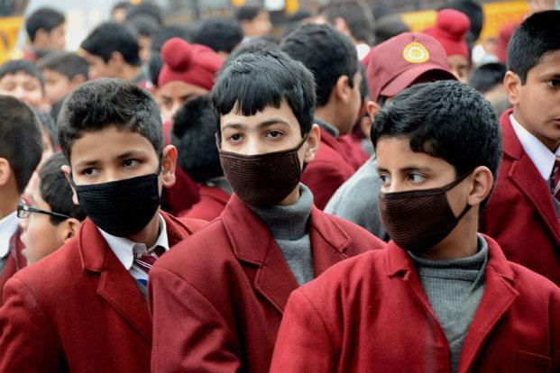 Students wearing swine flu masks on the first day of school after educational institutions re-opened following a five-and-a-half month break, in Srinagar this week. Photo: PTI