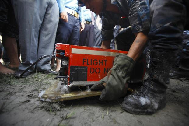 A Nepalese police officer carries a black box after it was recovered from the crash site of a Dornier aircraft, owned by private firm Sita Air, in Kathmandu September 2012. Photo: Reuters