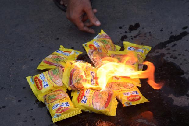 Indian social activists burn packets of Nestle's Maggi instant noodles during a protest in Kolkata on 4 June 2013. Photo: AFP