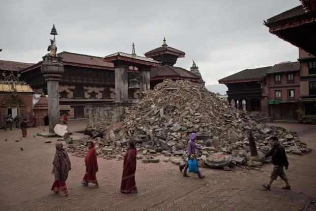 A file photo of people walking past damaged temples at the UNESCO world heritage site of Bhaktapur on the outskirts of Kathmandu, following an earthquake which struck Nepal on 25 April. Photo: AFP