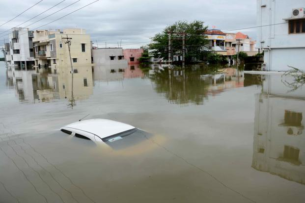 A car is submerged amidst water-logged houses in a rain-hit area of Chennai on 17 November. Photo: AFP