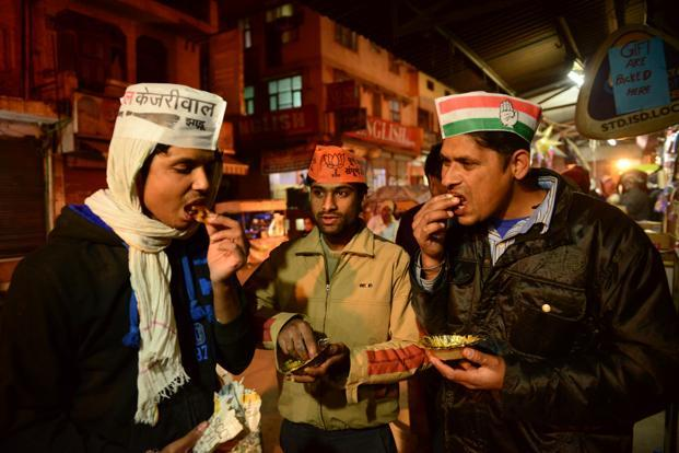 Rally volunteers of the major parties in the three-pronged political war between Congress, BJP and AAP for the Delhi assembly election are seen snacking on jalebee post campaign work. Photographed on 5 February 2015 by Pradeep Gaur.
