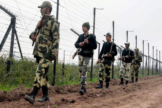 Border Security Force soldiers patrol the fence at Bamial border in Pathankot on Monday. Photo: PTI