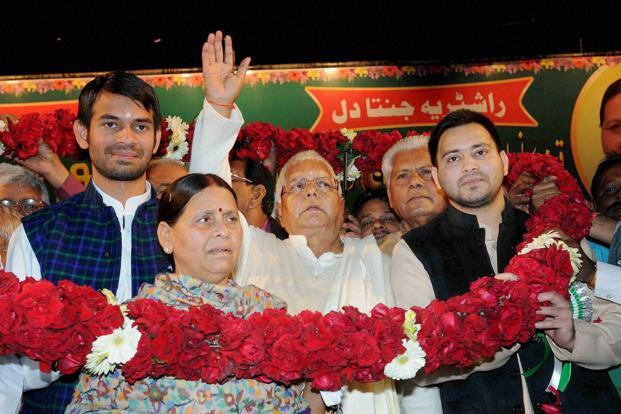 Lalu Prasad waves at supporters after he was re-elected as national president of Rashtriya